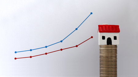 A miniature house on a pile of coins in front of a linear graph. Household income gap concept. Stock Photo