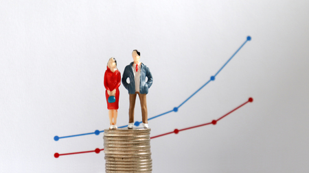 A miniature couple standing on a pile of coins in front of a flow linear graph. The concept is increasing the wage gap between men and women over time.