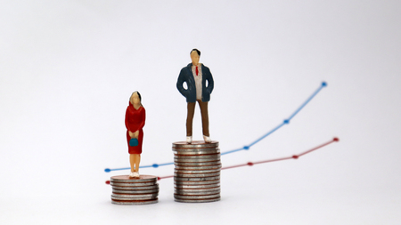 The concept of gender pay gap. A miniature man and a miniature woman standing on a pile of coins with a flow linear graph. Reklamní fotografie