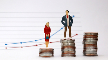 A miniature man and a miniature woman standing on a pile of coins with a flow linear graph. The concept of the wage gap between men and women in the workplace.