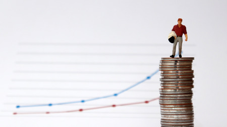 A miniature man standing on a pile of coins with a flow linear graph. The concept of the difference between the rate of inflation and the rate of wage increase. Stock Photo