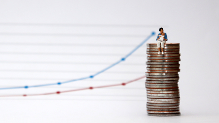 Flowing linear graph with a miniature woman sitting in a pile of coins holding a baby. The concept of wage discrimination against childcare women. Stock Photo
