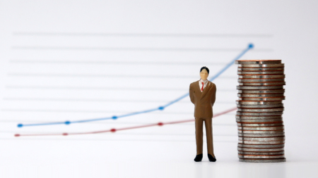 A pile of miniature man and coin stands in front of a linear graph. Stock Photo