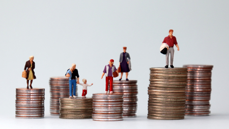 Miniature people standing on piles of different heights of coins. A concept of economic inequality. Stock Photo