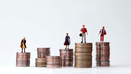 Miniature people standing on piles of different heights of coins. The concept of a growing income gap between individuals. Stock Photo