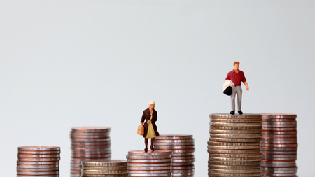 Miniature people standing on piles of different heights of coins. The concept of income gap. Stock Photo