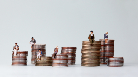 Miniature people standing on piles of different heights of coins. The concept of the income gap between individuals is not addressed. Stok Fotoğraf