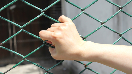 A womans hand grasping at the green iron fence.