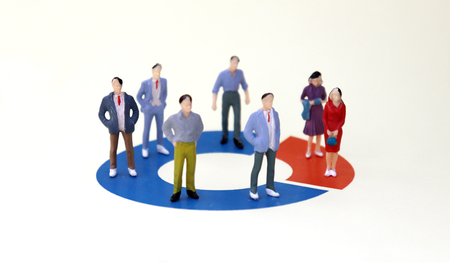 Miniature men and women standing on a donut graph. The concept of the difference between men and women in the enterprise. Standard-Bild