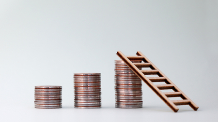 Three piles of coins and a small wooden ladder.