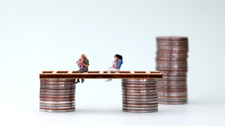 A miniature woman holding a baby and a pile of coins. Wage freeze concept for women. Stock Photo