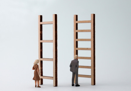 Miniature men and women standing in front of different ladders. The standard concepts are discriminatory against men and women in their work. Stock Photo