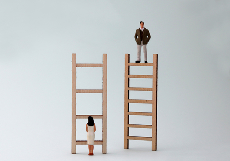 Wooden ladders and miniature people. The concept of gender inequality in promotion. Stock Photo