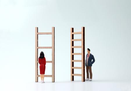 Miniaturmänner und -frauen, die vor verschiedenen Leitern stehen. Das Konzept der geschlechtsspezifischen Differenzierung zwischen Beförderung und Beschäftigung.
