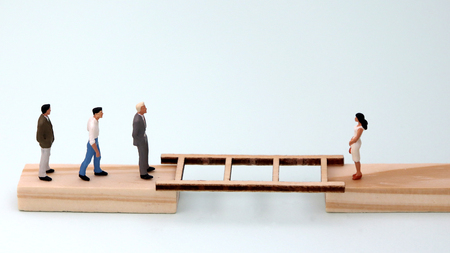 Miniature men and a miniature woman standing on wooden blocks with ladders between them. The concept of gender discrimination.