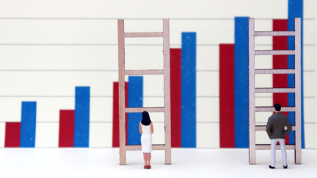 Bar charts and miniature people. The concept of gender discrimination in employment and wages.