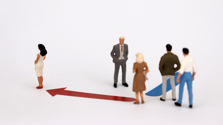 Two different directions and miniature people. The concept of discrimination between men and women in employment.