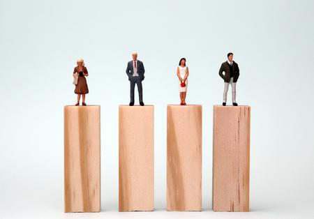 Hombres y mujeres en miniatura parados en el mismo bloque de altura. El concepto de igualdad de oportunidades de género. Foto de archivo