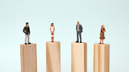 Miniature men and women standing on the same height block. The concept of equal opportunity for men and women.