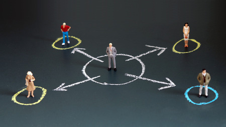 Miniature people each standing in a different circle. A concept of economic inequality.