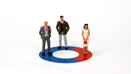 Two miniature men and a miniature woman are standing on a donut graph. A male-oriented social structure concept. Stock Photo