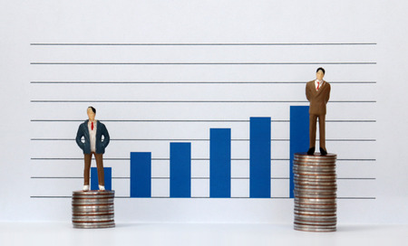 A miniature people standing on a pile of coins and a blue bar graph against the white background. The concept of individual gaps in promotion and employment.
