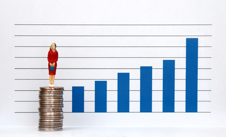 A miniature people standing on a pile of coins and a blue bar graph against the white background. The concept of women's pay improvement. Stock Photo