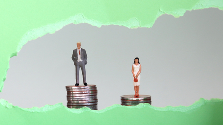 Miniature man and woman on pile of coins visible behind the green torn paper. The concept of discrimination in the workplace against invisible women.