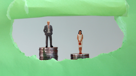 Miniature man and woman on pile of coins visible behind the green torn paper. The concept of discrimination between men and women in corporate advancement and wages.