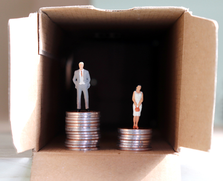 The concept of gender employment and wage differential. Miniature man and woman on pile of coins.