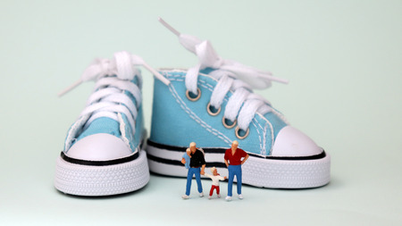 A miniature family with baby. Gay couple with baby sitting on miniature shoe. Banque d'images - 101143217