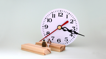 Same-sex marriage concept. The miniature gay couple is sitting on a wooden block in front of the clock.