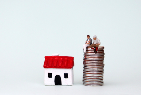 Homosexuality and family concept. The miniature gay couple is sitting on a pile of coins next to the miniature house.