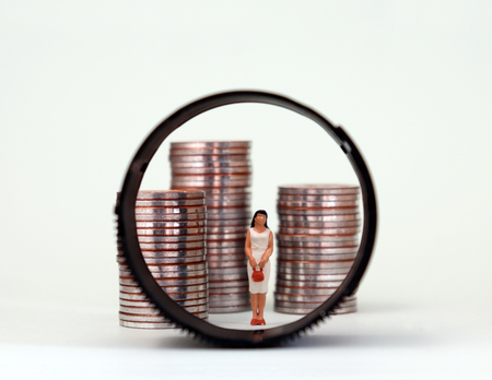 A miniature woman standing between three piles of coins. The changing concept of women and social conflict in modern times.