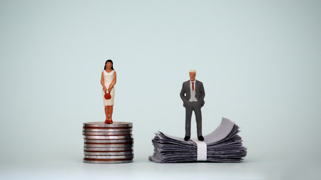 A miniature woman standing on a pile of coins and a miniature man standing on a pile of paper money. The concept of a gender pay gap.