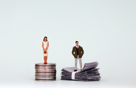 The concept of gender wage gap is used when a company by men and women. A miniature woman standing on a pile of coins and a miniature man standing on a pile of paper money.