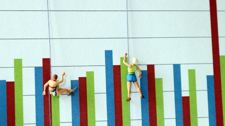 Miniature people climbing up a bar graph. A fierce job market concept.