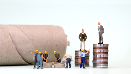 The miniature men are standing on top of a pile of coins and the miniature men working under it. Income difference and economic inequality concept. Stock Photo