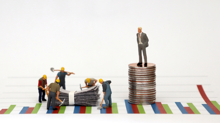 A man dressed in a suit standing on top of a pile of coins against a graph and miniature workers at a construction site below it. Stockfoto