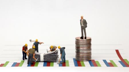 Un uomo vestito con un abito in piedi in cima a una pila di monete contro un grafico e lavoratori in miniatura in un cantiere sotto di esso.