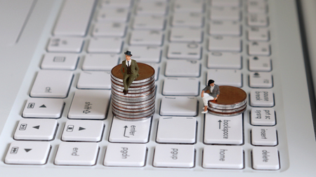 A miniature man sitting on a stack of coins on the backspace key. The concept of a gender promotion gap.