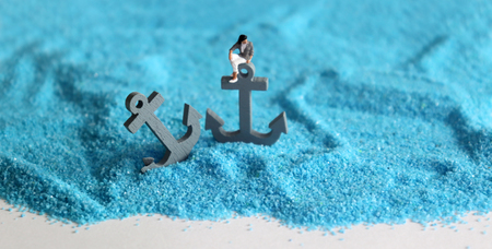 Two gray anchors on the blue sand with a miniature woman. Social restraint concept for women.