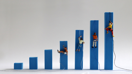 Miniature people climbing on hand blue bar graphs. A strong concept of employment and income differences. Reklamní fotografie