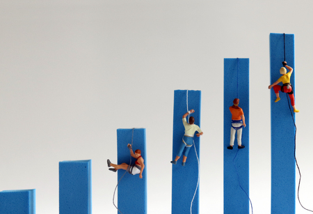 Miniature people climbing on hand blue bar graphs. The concept of competition for success. Фото со стока