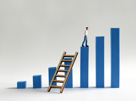 A miniature man walking across a bar of blue bar graph with a ladder across. The desire for promotion and success.