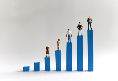 Five miniature people standing on a bar on a blue bar graph. Economic inequality and income gap concepts. Stock Photo