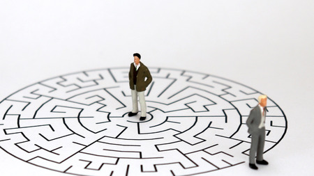 Miniature two men standing on a maze of white backgrounds.