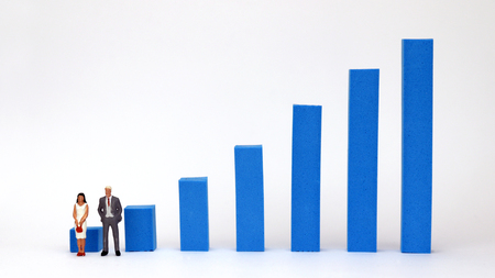 The miniature man and woman standing in front of the blue bar graph. Imagens