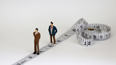 White tape measure with two miniature men.