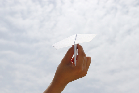 A paper airplane with a hand on a blue sky. A concept of dreams and passion.